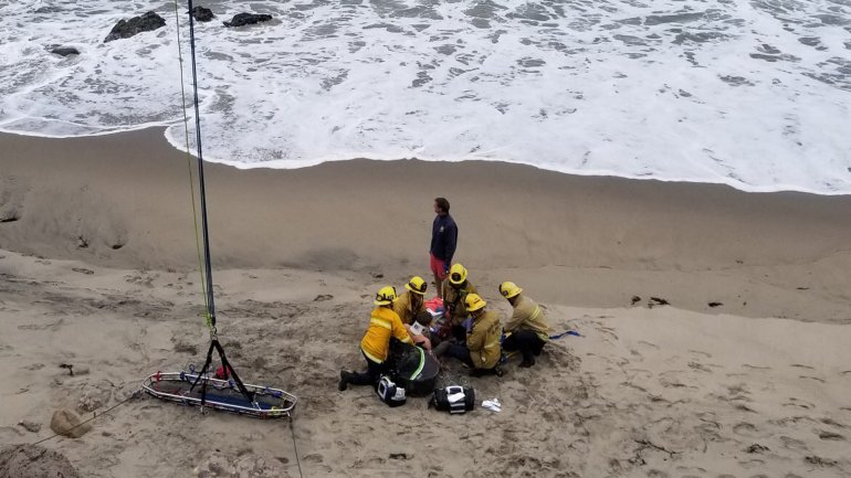 Firefighters treat a man who was injured in a crash landing in a hang glider along Pacific Coast Highway in Ventura County, near the Los Angels County line, on May 26, 2019. (Credit: Ventura County Fire Department)