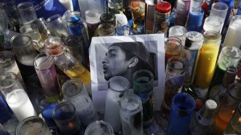 Candles surround a photograph of rapper Nipsey Hussle at a makeshift memorial in this undated photo. (Credit: Los Angeles Times)