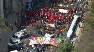 """Labor rights' advocates and other community groups rallied in celebration of """"May Day"""" in Los Angeles' MacArthur Park on May 1, 2019. (Credit: KTLA)"""
