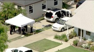 Officials inspect materials from the suspect's vehicle in Long Beach as seen in this image from Sky5 on June 11, 2019. (Credit: KTLA)