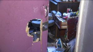 A hole can be seen in the door of one of the building's rooms. (Credit: KTLA)