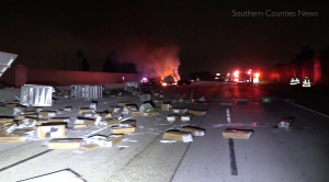 Packages are strewn across the northbound lanes of State Route 22 in Garden Grove as a big-rig burns following a crash on June 9, 2019. (Credit: Southern Counties News)