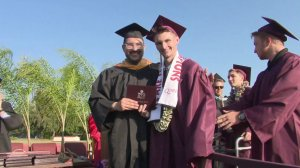 Alexander Harris, who is recovering from a broken neck, stepped out of his wheelchair to accept his diploma at Claremont High School on June 13, 2019. (Credit: KTLA)