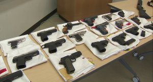 Guns seized during a two-year investigation into a San Pedro gang are shown on June 26, 2019. (Credit: KTLA)