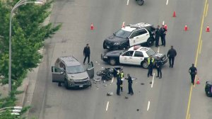 A SUV and a badly damaged LAPD motorcycle are shown at the scene of a crash in Van Nuys on June 14, 2019. (Credit: KTLA)