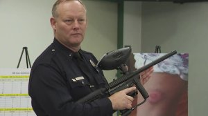 LAPD Lt. Jeff Bratcher holds a paintball gun during a news conference warning about their improper use on June 13, 2019. In the background, a victim's injury from a paintball gun in shown. (Credit: KTLA)