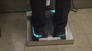 "An officer stands on ""Healthy Soles,"" a shoe-cleaning device on June 28, 2019, in LAPD's Central Division station. (Credit: KTLA)"