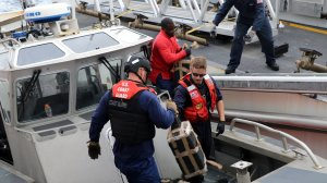 Crew members from the U.S. Coast Guard Cutter Monro transfer packages of cocaine from an interceptor boat to the cutter following an interdiction in the Eastern Pacific Ocean on June 6, 2019. (Credit: USCG)