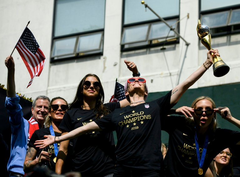 Megan Rapinoe (C), NY Mayor Bill de Blasio (L) and other members of the World Cup-winning US women's team take part in a ticker tape parade for the women's World Cup champions on July 10, 2019, in New York. (Credit: JOHANNES EISELE/AFP/Getty Images)
