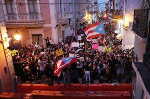 Protesters demonstrate against Ricardo Rossello, the governor of Puerto Rico, near where police are manning a barricade set up along a street leading to the governor's mansion on July 20, 2019, in Old San Juan, Puerto Rico. There have been calls for the governor to step down after it was revealed that he and top aides were part of a private chat group that contained misogynistic and homophobic messages. (Credit: Joe Raedle/Getty Images)