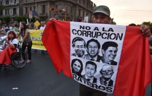 A man carries a flag with the faces of former Peruvian presidents Alberto Fujimori, Alejandro Toledo and Alan Garcia, former first lady Nadine Heredia and her husband, former president Ollanta Humala, and current President Pedro Pablo Kuczynski, while thousands march against corruption through the streets of downtown Lima, Peru on Feb. 16, 2017. (Credit: CRIS BOURONCLE/AFP/Getty Images)