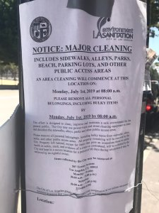 A flier posted on a pole in downtown Los Angeles announces a clean up on July 1, 2019. (Credit: KTLA)
