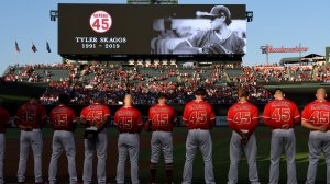 The Los Angeles Angels of Anaheim stand for a moment of silence before they play the Seattle Mariners at Angel Stadium of Anaheim on July 12, 2019 in Anaheim, California. The entire Angels team wore #45 on their jersey to honor Skaggs who died on July 1. (Credit: John McCoy/Getty Images)