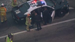 A person who led authorities on a pursuit sits inside a police vehicle after officers took him into custody in Alhambra on Aug. 12, 2019. (Credit: Sky5)
