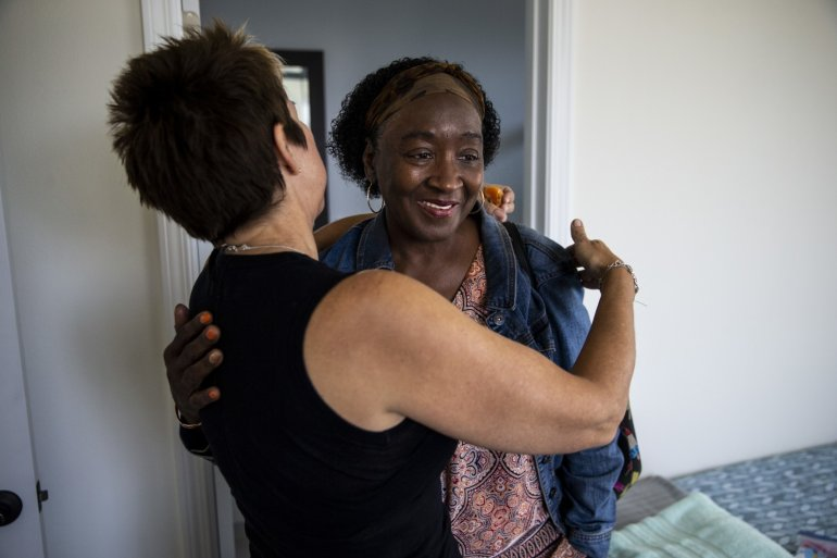 Patricia Wilson gets a hug from Heidi Roberts, left, as she and other tenants move into their new home along Wall Street in April 2018 in Los Angeles. (Credit: Kent Nishimura / Los Angeles Times)