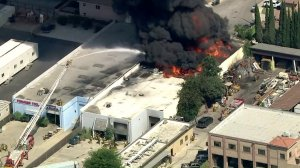 Firefighters battle a massive blaze at a commercial building in Paramount on Aug. 19, 2019. (Credit: KTLA)