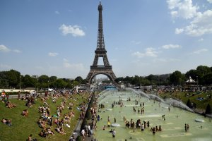 People cool off and sunbathe by the Trocadero Fountains next to the Eiffel Tower in Paris, on July 25, 2019 as a new heatwave hits the French capital. (Credit: BERTRAND GUAY/AFP/Getty Images)