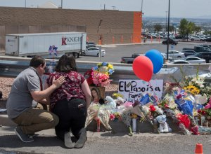 People pray beside a makeshift memorial outside the Cielo Vista Mall Wal-Mart where a shooting left 20 people dead in El Paso, Texas, on Aug. 4, 2019. (Credit: MARK RALSTON/AFP/Getty Images)