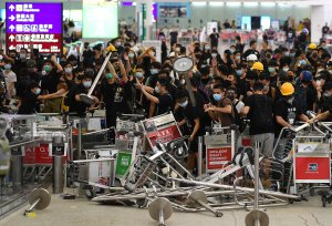Pro-democracy protestors block the entrance to the airport terminals after a scuffle with police at Hong Kong's international airport late on Aug. 13, 2019. (Credit: MANAN VATSYAYANA/AFP/Getty Images)