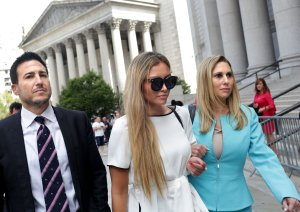 Jennifer Araoz, center, one of deceased financier Jeffrey Epstein's alleged victims, and her attorney Kimberly Lerner, right, finish speaking to the press outside federal court in New York City on Aug. 27, 2019. (Credit: Yana Paskova / AFP / Getty Images)