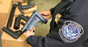 A CBP officer inspects one of the firearms parts seized at the LA/Long Beach Seaport (Credit: U.S. Customs and Border Protection)