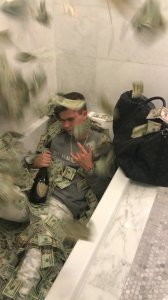 Sitting a tub filled with bills of money, 22-year-old Wyatt Pasekis appears in an undated photo released by the U.S. Department of Justice on Aug. 26, 2019.