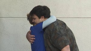 Ben Kadish hugs Cathy Carter, the nurse who helped save him after he was shot at the North Valley Jewish Community in Granada Hills on Aug. 10, 1999. They met outside the hospital where he was treated, Providence Holy Cross Medical Center in Mission Hills, on Aug. 7, 2019. (Credit: KTLA)