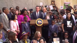 Gov. Gavin Newsom is surrounded by those who've lost family members to police shootings as he signs AB 392 on Aug. 19, 2019, in a still from a livestream shared by state Sen. Toni Atkins.