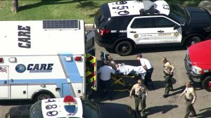A man who authorities say struck a deputy as he led officers on a chase in South Gate is escorted into an ambulance after the pursuit ended in a neighborhood in Bellflower on Aug. 2, 2019. (Credit: KTLA)
