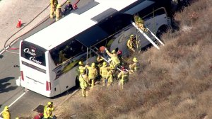 Firefighters work to get passengers off a charter bus after a crash on the 118 Freeway in Simi Valley on Sept. 3, 2019. (Credit: KTLA)