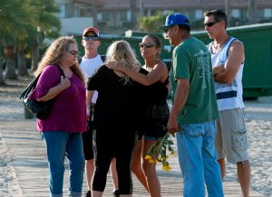 People embrace beside a memorial wall near the Truth Aquatics moorings where the boat that burned and sank off the Santa Cruz islands early in the morning, was based in Santa Barbara, Sept. 2, 2019. (Credit: MARK RALSTON/AFP/Getty Images)