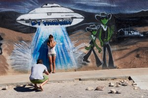 Visitors take photos in front of a mural depicting aliens and a spaceship outside ET Fresh Jerky in Hiko, Nevada, on Sept. 13, 2019. (Credit: Bridget Bennett / AFP / Getty Images)