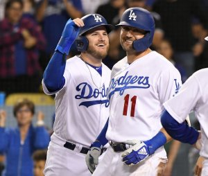 Max Muncy of the Los Angeles Dodgers celebrates with A.J. Pollock during a game against the Colorado Rockies at Dodger Stadium on Sept. 20, 2019. (Credit: John McCoy/Getty Images)