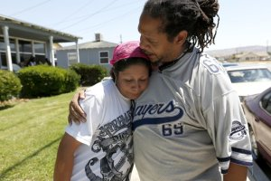 Roberta Alcantar, left, mother of the victim, is comforted by Pharaoh Mitchell, co-founder of the Community Action League, in Palmdale in this undated photo.(Credit: Gary Coronado / Los Angeles Times)