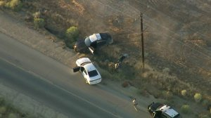 A man who stole a CHP vehicle during a wild pursuit in the Antelope Valley is surrenders to police west of Rosamond on Oct. 2, 2019. (Credit: KTLA)