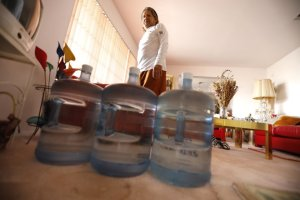 "Ruben Mendez stands with water jugs in his home, located about a mile east of the March Air Reserve Base in Riverside County, in 2019. ""We thought we had nice, clean water,"" he said.(Credit: Genaro Molina / Los Angeles Times)"
