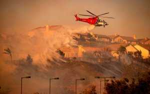 A helicopter drops water to help fight flames during the Saddleridge Fire in Porter Ranch on Oct. 11, 2019.(Credit: Josh Edelson/AFP via Getty Images)