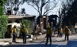 Firefighters gather their hoses near destroyed homes along North Tigertail Road during the Getty Fire on Oct. 29, 2019. (Credit: FREDERIC J. BROWN/AFP via Getty Images)