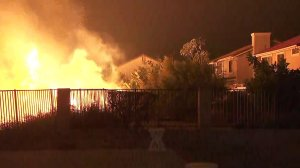 Flames burn dangerously close to a home in Porter Ranch on Oct. 11, 2019. (Credit: KTLA)