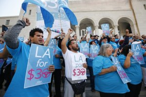 Uber driver Joel Carbonell, left, and Lyft driver Eduardo Belalcazar, center, cheer outside Los Angeles City Hall on Oct. 15, 2019 after lawmakers agreed to study a minimum hourly wage for drivers.(Credit: Al Seib / Los Angeles Times)