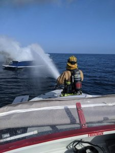 A Harbor Patrol first responder in Orange County hoses down a boat fire 10 miles off the Newport Coast on Oct. 18, 2019. (Credit: Orange County Sheriff's Department)