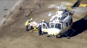 Rescuers work at the scene of a collision involving public works employees in the Santa Monica Mountains near Agoura Hills on Oct. 3, 2019. (Credit: KTLA)