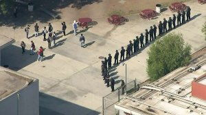 Police officers stand guard at John C. Fremont High School in the Florence neighborhood of the South L.A. area after multiple fights were reported at the campus on Nov. 12, 2019. (Credit: KTLA)