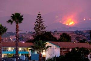 The Cave Fire burns a hillside above houses in Santa Barbara on Nov. 26, 2019. (Credit: KYLE GRILLOT/AFP via Getty Images)