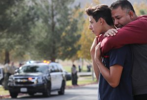 Marco Reynoso, right, hugs his son, 11th-grader Dylan Reynoso, after reuniting at a park near Saugus High School after a shooting left two students dead and three wounded on Nov. 14, 2019. (Credit: Mario Tama / Getty Images)