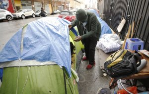 John Gunn looks into his tent on Skid Row after rain and hail soaked his belongings on Nov. 20, 2019. (Credit: Al Seib / Los Angeles Times)