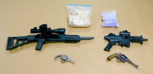 Guns and drugs seized at the Santa Ana home of Antonio Silva, a homicide and kidnapping suspect, are seen in a photo released Nov. 20, 2019, by the Anaheim Police Department.