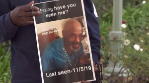 A family member holds a flyer showing Douglas James, who's been missing since being dropped off in the West Carson area by California Highway Patrol on Nov. 5, during a press conference on Nov. 21, 2019. (Credit: KTLA)