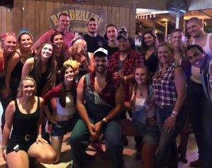 In this photo provided by family to CNN in November 2019, Justin Meek, center, poses with his sister, below right, and his friends at Borderline Bar & Grill in Thousand Oaks.