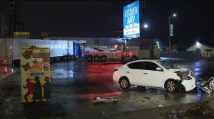 A heavily damaged sedan is seen near a big rig that had crashed into a liquor store in the North Hollywood area on Dec. 23, 2019. (Credit: KTLA)